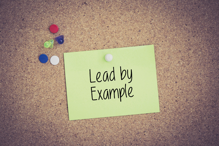example: Lead by Example written on sticky note pinned on pinboard Stock Photo