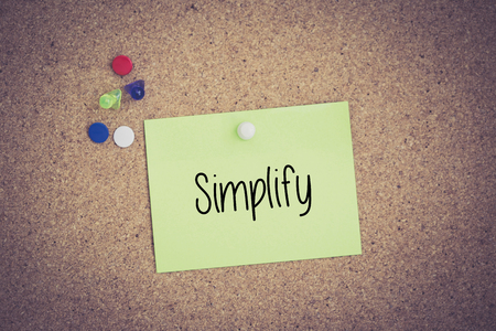 pragmatic: Simplify written on sticky note pinned on pinboard Stock Photo