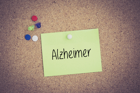 alzheimer: Alzheimer written on sticky note pinned on pinboard Stock Photo