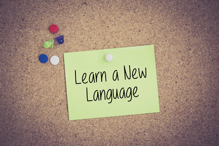 Learn A New Language written on sticky note pinned on pinboard