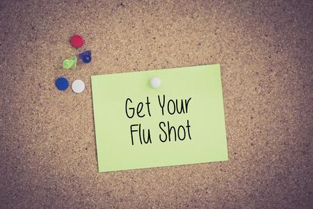 swine flu vaccinations: Get Your Flu Shot written on sticky note pinned on pinboard