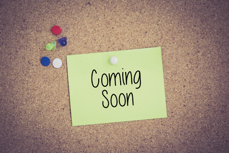 presently: Coming Soon written on sticky note pinned on pinboard Stock Photo
