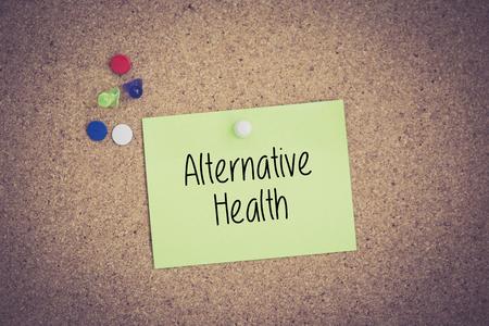 alternative health: Alternative Health written on sticky note pinned on pinboard