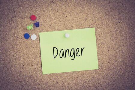 hazardous area sign: Danger written on sticky note pinned on pinboard