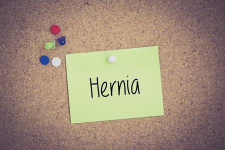 hernia: Hernia written on sticky note pinned on pinboard