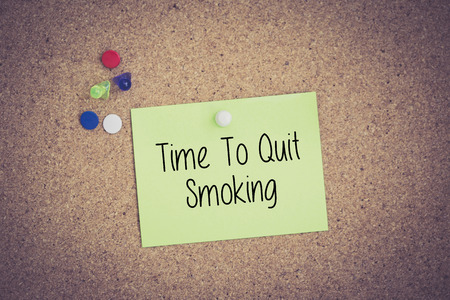 conclude: Time To Quit Smoking written on sticky note pinned on pinboard Stock Photo