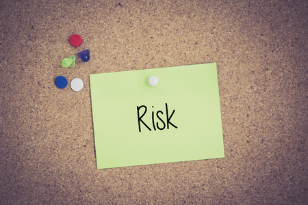 risky situation: Risk written on sticky note pinned on pinboard Stock Photo