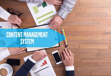 management system: BUSINESS TEAM WORKING OFFICE CONTENT MANAGEMENT SYSTEM DESK CONCEPT Stock Photo