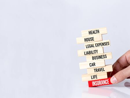 building insurance: Businessman Building INSURANCE concept with Wooden Blocks