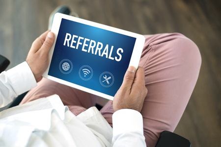 referidos: People using tablet pc and REFERRALS concept on screen