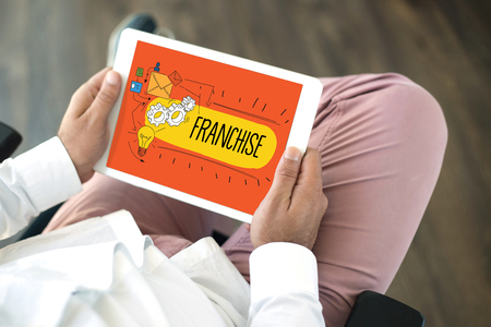 franchising: People using tablet pc in office and FRANCHISE concept on screen