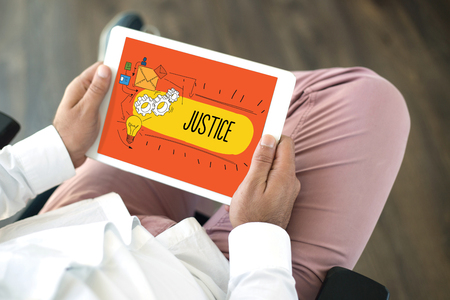 judicature: People using tablet pc in office and JUSTICE concept on screen