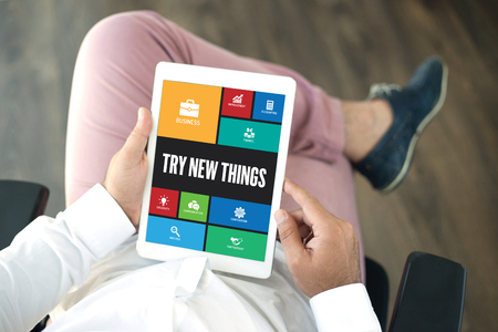 in need of space: People using tablet pc in office and TRY NEW THINGS icons concept on screen Stock Photo