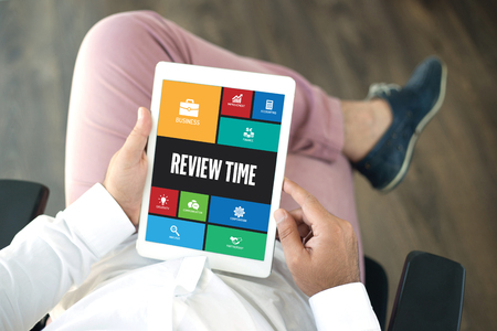 reassessment: People using tablet pc in office and REVIEW TIME icons concept on screen