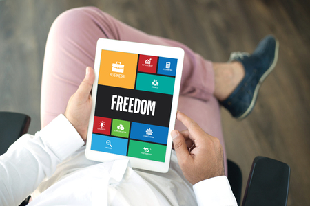freedom concept: People using tablet pc in office and FREEDOM icons concept on screen