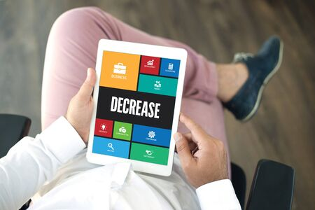 depreciation: People using tablet pc in office and DECREASE icons concept on screen Stock Photo