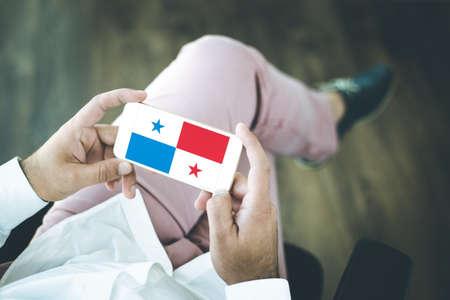 bandera de panama: Las personas que usan el teléfono inteligente y que muestran en la pantalla de la bandera de PANAMÁ Foto de archivo