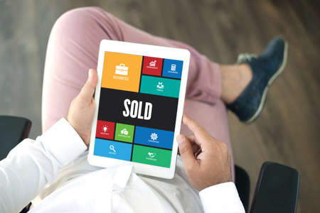 special agent: People using tablet pc in office and SOLD icons concept on screen Stock Photo