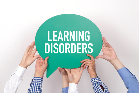 disorders: Group of people holding the LEARNING DISORDERS written speech bubble