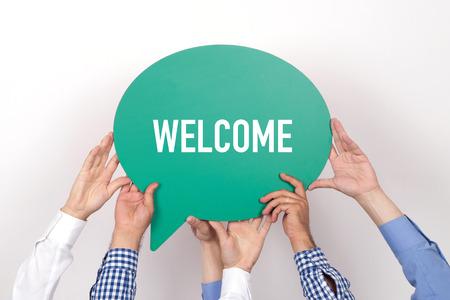 Groep mensen houden van de WELCOME geschreven tekstballon Stockfoto