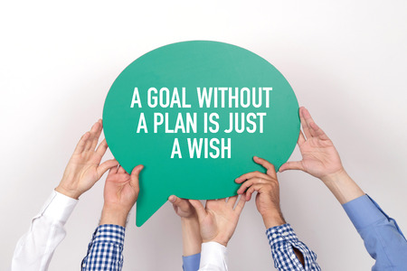 strategic focus: Group of people holding the A GOAL WITHOUT A PLAN IS JUST A WISH written speech bubble