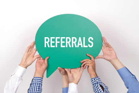 referidos: Group of people holding the REFERRALS written speech bubble
