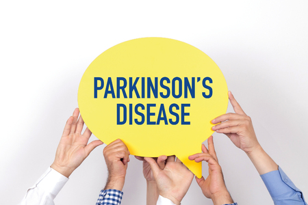 motor neuron: Group of people holding the PARKINSONS DISEASE written speech bubble