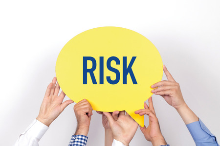 risky situation: Group of people holding the RISK written speech bubble