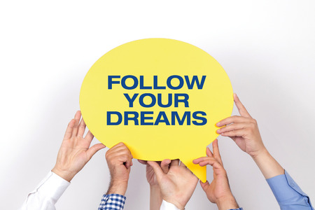 motivator: Group of people holding the FOLLOW YOUR DREAMS written speech bubble Stock Photo