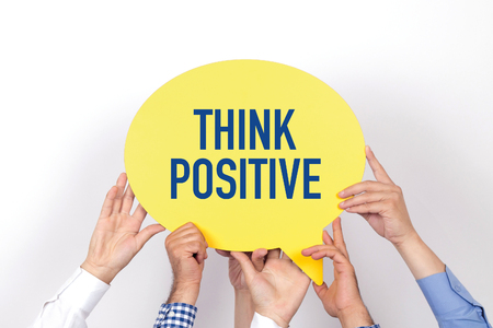 different goals: Group of people holding the THINK POSITIVE written speech bubble