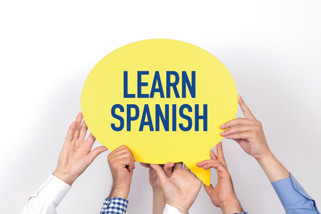Group of people holding the LEARN SPANISH written speech bubble