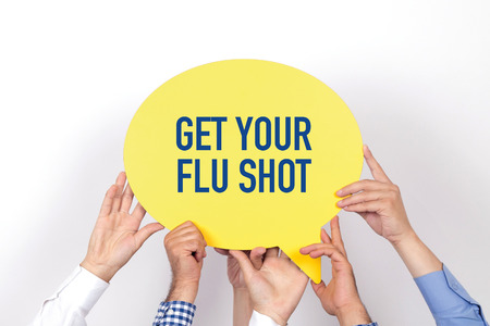 swine flu vaccination: Group of people holding the GET YOUR FLU SHOT written speech bubble Stock Photo