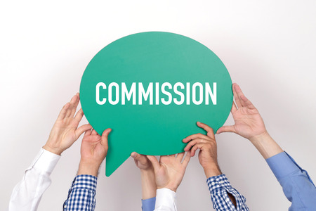 commission: Group of people holding the COMMISSION written speech bubble Stock Photo