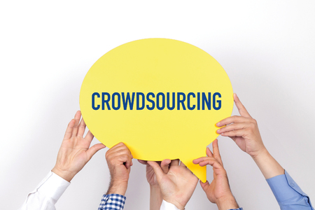 crowd source: Group of people holding the CROWDSOURCING written speech bubble Stock Photo