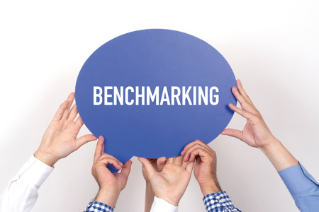 benchmarking: Group of people holding the BENCHMARKING written speech bubble