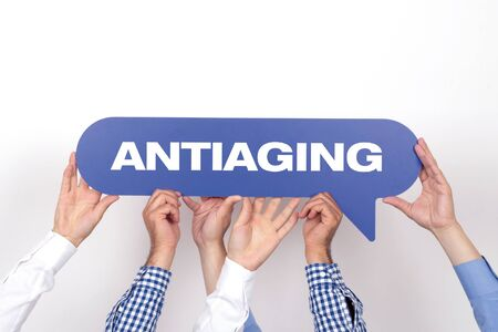 elasticidad: Group of people holding the ANTIAGING written speech bubble