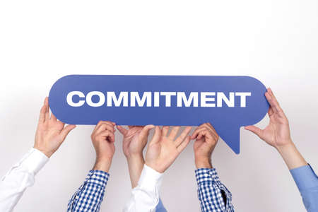 obligate: Group of people holding the COMMITMENT written speech bubble Stock Photo