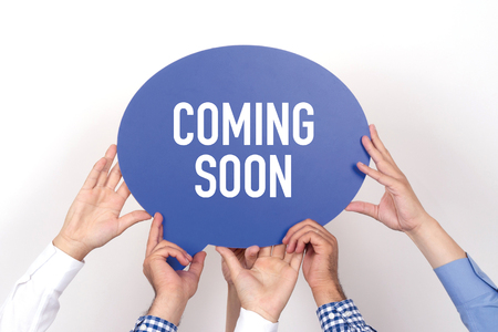 presently: Group of people holding the COMING SOON written speech bubble