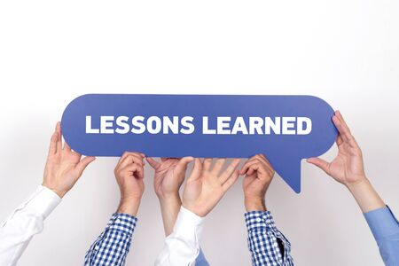 learned: Group of people holding the LESSONS LEARNED written speech bubble Stock Photo