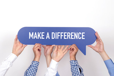 Group of people holding the MAKE A DIFFERENCE written speech bubble Stock Photo