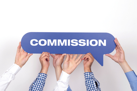 commercial law: Group of people holding the COMMISSION written speech bubble Stock Photo