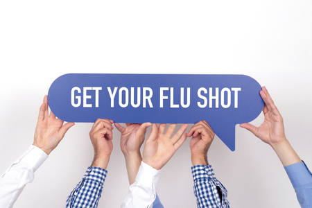 swine flu vaccinations: Group of people holding the GET YOUR FLU SHOT written speech bubble Stock Photo