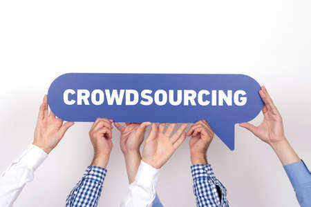 Group of people holding the CROWDSOURCING written speech bubble Stock Photo