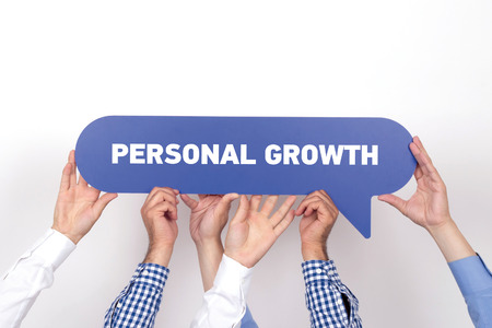 crecimiento personal: Group of people holding the PERSONAL GROWTH written speech bubble