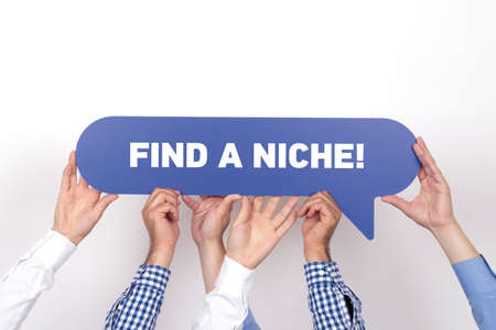 specialize: Group of people holding the FIND A NICHE! written speech bubble Stock Photo