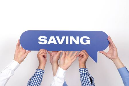 frugality: Group of people holding the SAVING written speech bubble Stock Photo