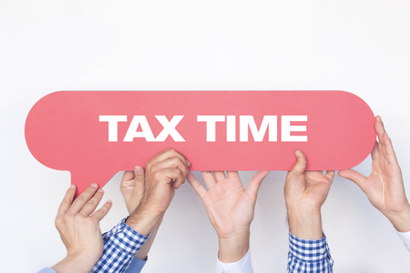 exemption: Group of people holding the TAX TIME written speech bubble Stock Photo