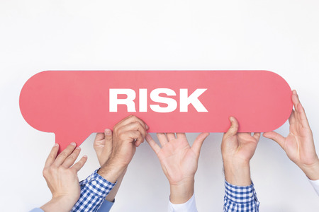risky situation: Group of people holding the Risk written speech bubble Stock Photo