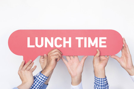 take time out: Group of people holding the LUNCH TIME written speech bubble Stock Photo