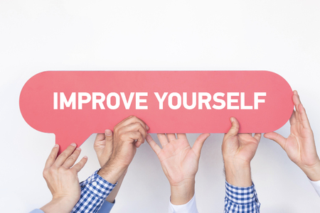 enrich: Group of people holding the IMPROVE YOURSELF written speech bubble Stock Photo